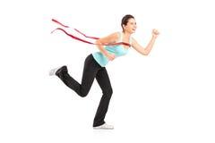 Weiblicher Seitentrieb, der ein Marathon gewinnt Stockfotografie