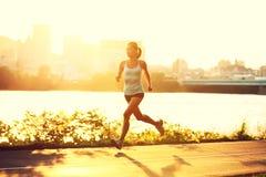 Weiblicher Seitentrieb, der am Sonnenuntergang läuft Stockfoto