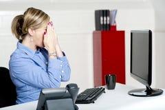 Weiblicher Sekretär, der ihr Gesicht mit den Händen versteckt Lizenzfreies Stockfoto