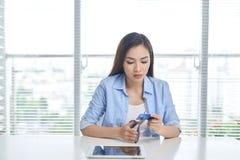 Weiblicher shopaholic Ausschnitt ihre Kreditkarte mit Scheren lizenzfreie stockfotos