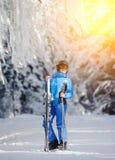 Weiblicher Skifahrer auf einer Skisteigung an einem sonnigen Tag Stockfotografie
