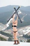 Weiblicher Skifahrer, der auf die Oberseite der Steigung steht und Skis über Kopf hält Tragender Badeanzug, Stiefel Makro des grü Lizenzfreie Stockfotografie