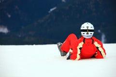 Weiblicher Skifahrer, der auf Hügel liegt Lizenzfreie Stockfotos