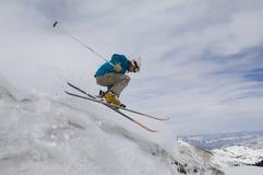 Weiblicher Skifahrer, der weg vom eisigen Überhang springt lizenzfreies stockbild