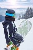 Weiblicher Snowboarder, der mit Snowboard in einer Hand steht und alpine Berglandschaft genießt Snowboardingkonzept Lizenzfreie Stockfotos