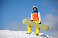 Weiblicher Snowboarder gegen Sonne und Himmel lizenzfreie stockbilder