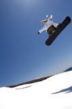 Weiblicher Snowboarder springen von hinten beleuchtetes Stockbilder