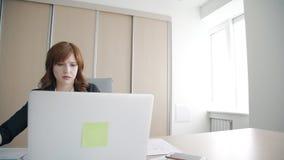 Weiblicher Spezialist arbeitet mit Laptop und Dokumenten bei Tisch im modernen Büro stock video