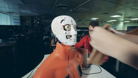 Weiblicher Spezialist justiert eine menschlich ähnliche Maske auf dem Gesicht eines Roboters stock footage