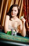 Weiblicher Spieler am spielenden Tisch mit Chips Lizenzfreies Stockfoto