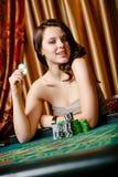 Weiblicher Spieler am Tisch mit Chips Stockfoto