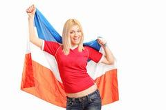 Weiblicher Sportfan, der eine niederländische Flagge wellenartig bewegt Lizenzfreie Stockfotos