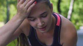 Weiblicher Sportlerläufer wischt Schweiß nach hartem Training draußen, Zeitlupe ab stock video