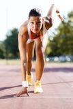 Weiblicher Sprinter, der zum Lauf fertig wird Stockfotografie