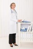 Weiblicher Standplatz des älteren Doktors im Büroportrait Stockfotografie