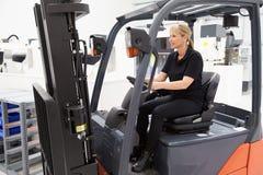 Weiblicher Staplerfahrer Working In Factory Lizenzfreie Stockfotografie
