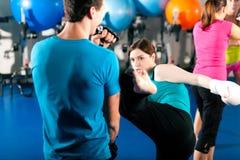 Weiblicher Stoßboxer mit Kursleiter beim sparring stockbild