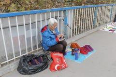 Weiblicher Straßenverkäufer, der handgemachte starke Baumwollschuhe im Winter, luftgetrockneten Ziegelstein rgb verkauft Stockbild