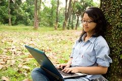 Weiblicher Student, der an einem Laptop arbeitet Stockbilder