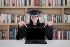Weiblicher Student im Aufbaustudium, der auf copyspace zeigt Stockfotos