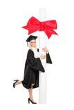 Weiblicher Student im Aufbaustudium, der mit einem enormen Diplom aufwirft Stockbilder