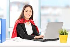 Weiblicher Superheld, der an Laptop in einem Büro arbeitet Stockfotografie