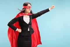 Weiblicher Superheld mit der angehobenen Faust Stockfotografie