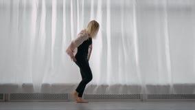 Weiblicher Tänzer der professionellen modernen Art, der am Fenster im Studio probt stock video
