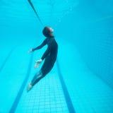 Weiblicher Taucher, der unter Wasser fliegt Stockbild