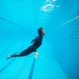 Weiblicher Taucher, der unter Wasser fliegt Lizenzfreie Stockbilder