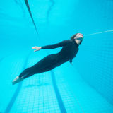 Weiblicher Taucher, der unter Wasser in Swimmingpool fliegt Stockfoto