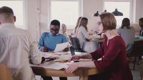 Weiblicher Teamleiter erklärt Diagrammblatt männlichem Angestelltem Multiethnische Teambesprechung am gesunden Arbeitsplatz des m stock video footage