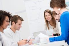Weiblicher Teamleiter mit ihrem Geschäftsteam Stockbild