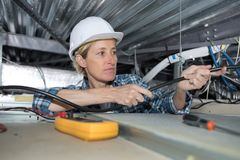Weiblicher Techniker, der Klimaanlage in der Decke überprüft Stockfotografie