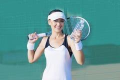 Weiblicher Tennis-Spieler, der mit Wasser-Flasche beim Gericht und bei Smili aufwirft Lizenzfreie Stockfotografie