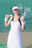 Weiblicher Tennis-Spieler, der mit Wasser-Flasche am Gericht aufwirft Lizenzfreie Stockfotos