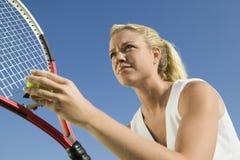 Weiblicher Tennis-Spieler, der sich vorbereitet zu dienen stockfotos