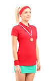 Weiblicher Tennisspieler des Siegers mit einer goldenen Medaillenstellung Stockfotografie