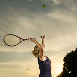 Weiblicher Tennisspieler ungefähr, zum des Balls zu dienen Stockfotos