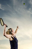 Weiblicher Tennisspieler ungefähr, zum des Balls zu dienen Lizenzfreie Stockbilder