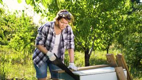 Weiblicher Tischler im überprüften Hemd, das hölzerne Planke im Sommergarten sägt stock video