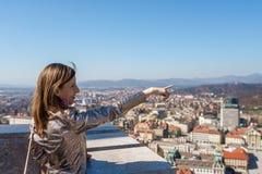 Weiblicher Tourist, der auf eine Anziehungskraft in der Stadt von Ljubljana zeigt lizenzfreie stockfotografie