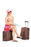 Weiblicher Tourist, der eine Karte hält und auf ihrem Gepäck sitzt Lizenzfreies Stockfoto