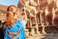 Weiblicher Tourist mit dem Smartphone, der Foto von Angkor-Tempel macht Stockfotografie