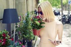 Weiblicher Tourist mit dem Stadtplan, der draußen Topf rote Blumen am sonnigen Tag der Erholung im Sommer hält Lizenzfreie Stockfotos