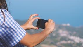 Weiblicher Tourist vertritt Foto am Telefon die wunderbar schöne Ansicht des blauen Meeres und der Berge Abschluss oben Stockfotografie