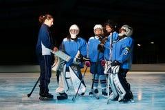 Weiblicher Trainer, der Strategie mit Hockey-Team wiederholt lizenzfreie stockbilder