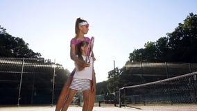 Weiblicher Trainer, der wenig Mädchen spielt Tennis auf dem Gericht unterrichtet stock video