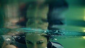 Weiblicher Trainer oder Mutter unterrichten ein wenig todler, um unter dem Wasser zu tauchen Hält ihn über dem Tauchen des Wasser stock video