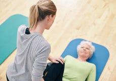 Weiblicher Trainer, welche der älteren Frau trainiert in der Turnhalle hilft Lizenzfreies Stockfoto